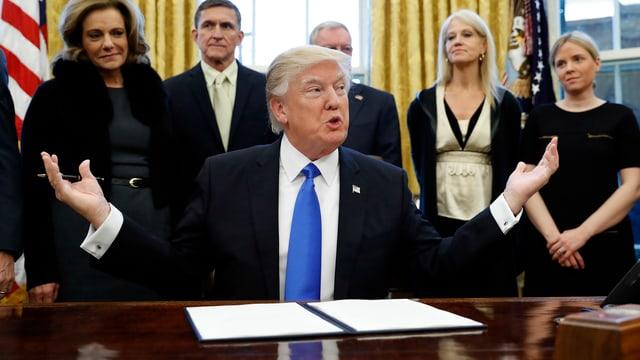 Donald Trump sitzt an einem Tisch.