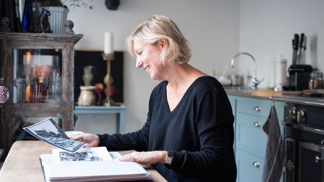 Eine Frau sitzt am Tisch in ihrer Küche.