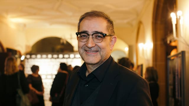 Ein Mann mit Brille, lächelnd
