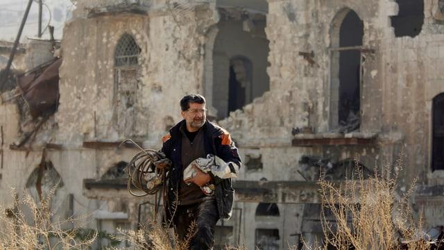 Zu sehen ist ein Mann in den Ruinen von Aleppo.