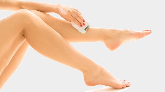 Frau epiliert sich die Beine.