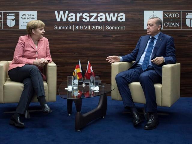 Merkel (links) und Erdoga sitzen auf schweren Stühlen und sprechen zueinander. Auf einem kleinen Tisch hat es zwei Fähnchen der beiden Länder.