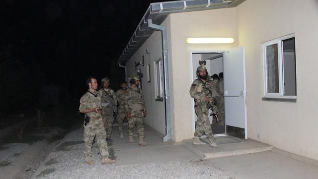 Soldaten stehen in der Nacht vor einem Haus