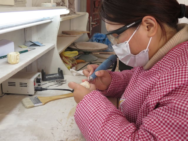 Elfenbeinschnitzerin bei der Arbeit mit einem Zahnborer.
