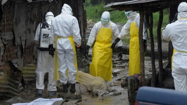 Männer in Schutzkleidung stehen an einem leblosen Körper.