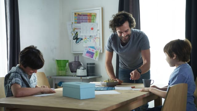 Mann mit zwei Kindern am Tisch