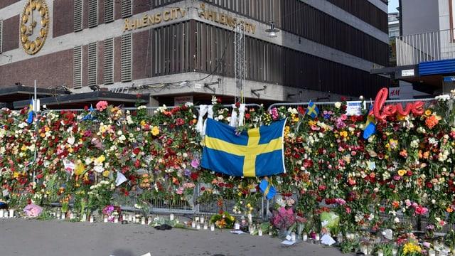 Zahlreiche Blumen und Kerzen wurden an einem Gitter angebracht.