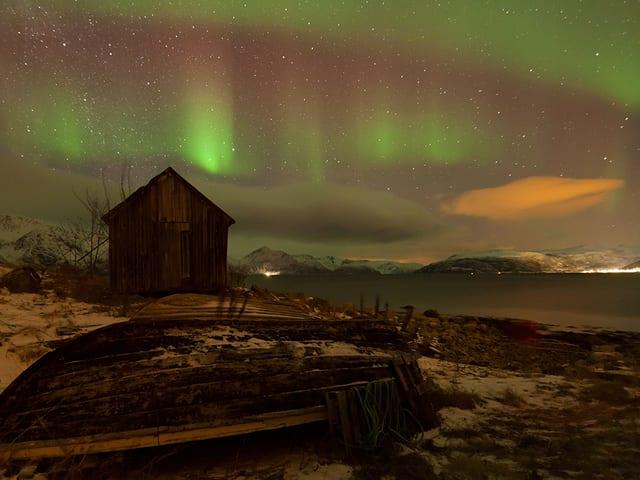 Eine Hütte und ein Holzboot im Licht eines Polarlichts