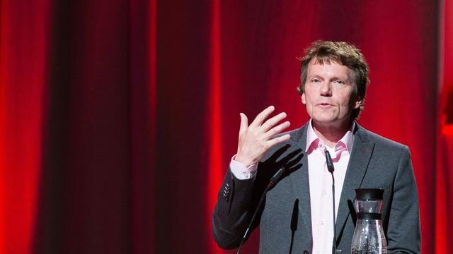 Hartmut Rosa in Anzug vor einem roten Vorhang bei einer Rede
