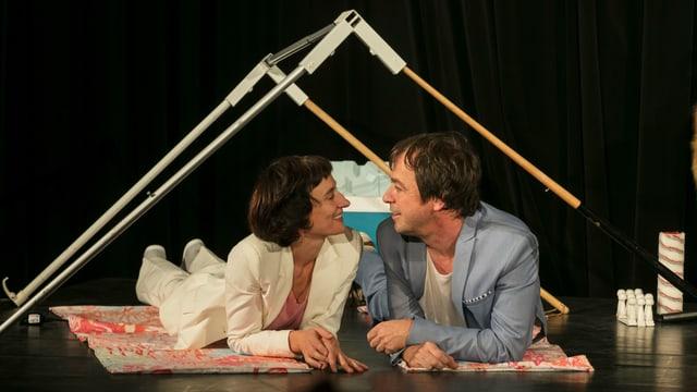 Ein Mann und eine Frau liegen unter einen selbst gebauten Zelt auf einer Bühne.
