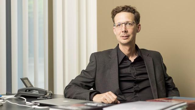 Politologe Michael Hermann sitzt an seinem Schreibtisch.