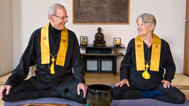 Brantschen und Gyger sitzen im Lotus-Sitz nebeneinander und schauen sich gegenseitig an.
