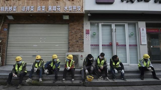 Arbeiter in der Provinz Hubei machen Pause vor geschlossenen Restaurants.