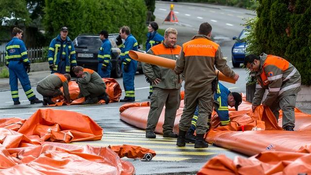 Zivilschützer und Feuerwehrleute stehen zwischen orangen Plastikschläuchen