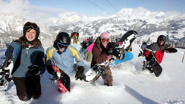 Jugendliche sind mit ihren Snowboards im tiefen Schnee unterwegs.