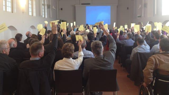 Mehrere Versammlungsteilnehmer stimmen mit gelben Zetteln ab.