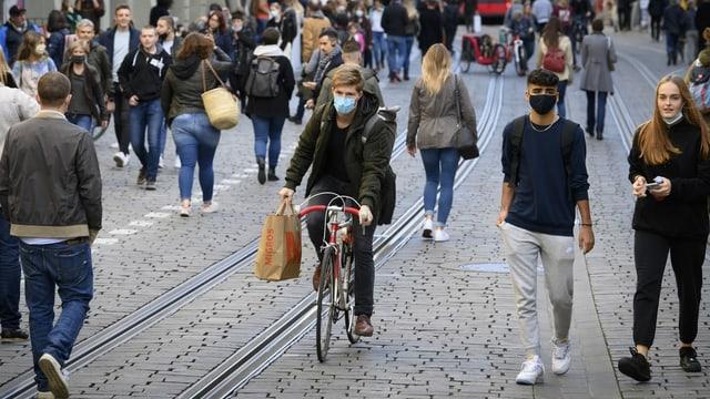 Viele Fussgänger und ein Velofahrer unterwegs in einer Gasse in der Berner  Altstadt.