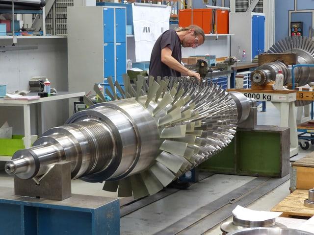 Ein Arbeiter arbeitet an einer metallischen Turbine.