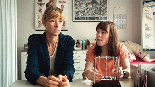 Eine Frau sitzt angestrengt nachdenkend am Tisch, neben ihr die Tochter, sie ansehend.