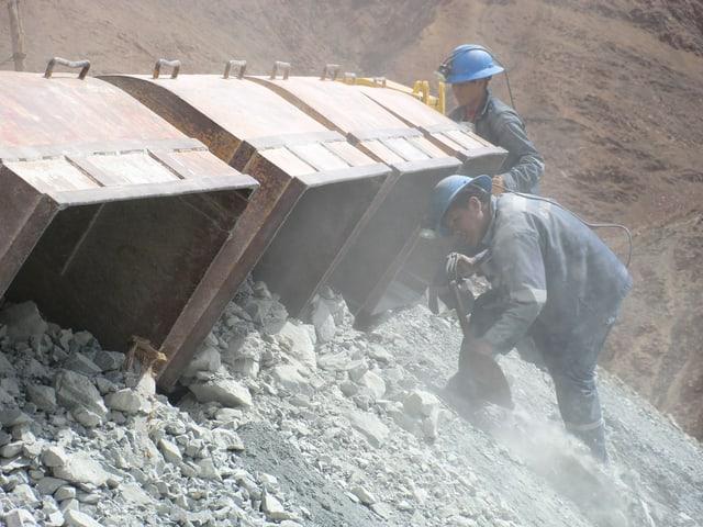 Dus miniers stgargian crappa che cuntegn particlas dad aur.