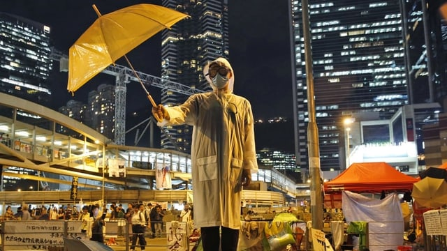 Ein Demonstrant mit einem gelben Regenschirm