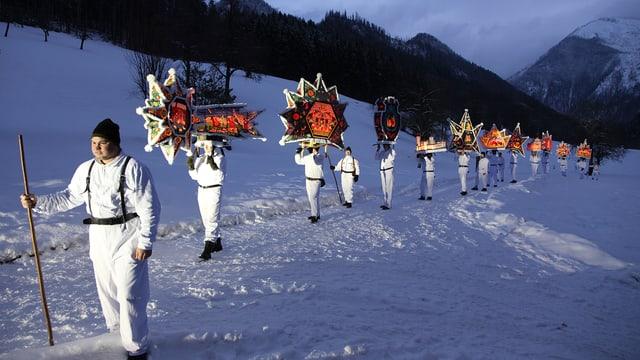 Umzug: Männer in weissen Gewändern und mit grossen leuchtenden Kappen auf dem Kopf gehen durch den Schnee..