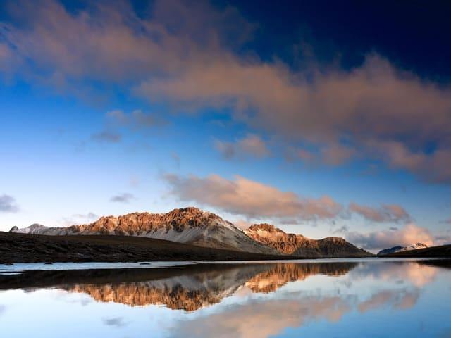 Blick über einen See mit Schneebergen im Hintergrund