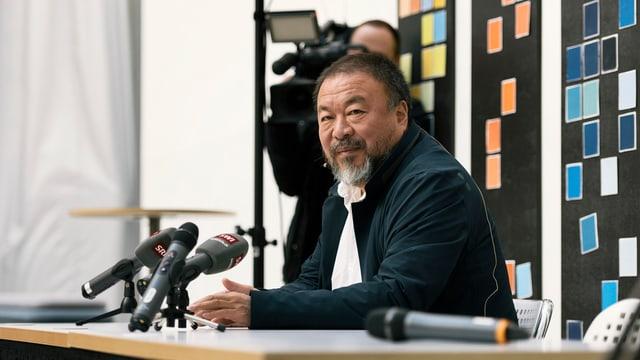 Ai Weiwei im Porträt an einem Pult.