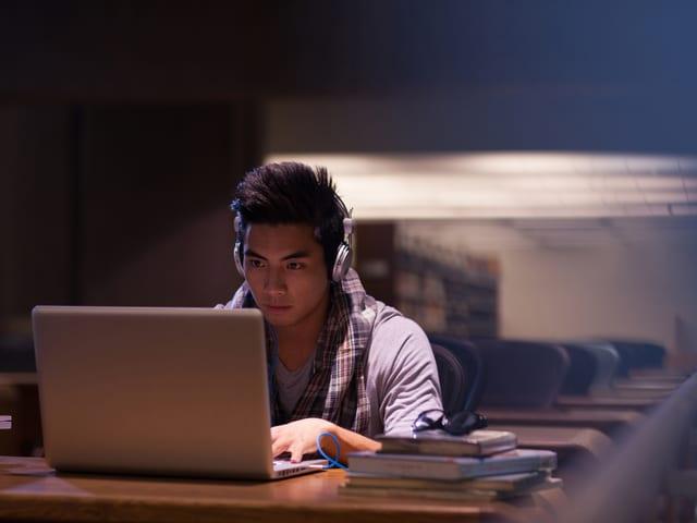 Jugendlicher mit Laptop und Kopfhörer im Lesesaal einer Bibliothek.