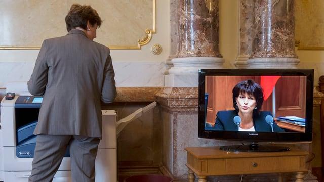 Ina dunna guarda sin ina televisiun che mussa Doris Leuthard
