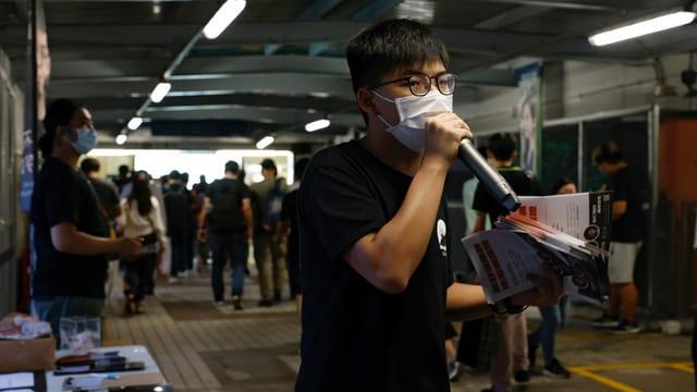 Wong trägt eine Hygienemaske, hat Flyer in der Hand und spricht in ein Mikrofon.
