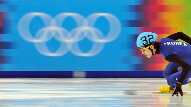 Olympia Ringe hinter einem Eisschnellläufer