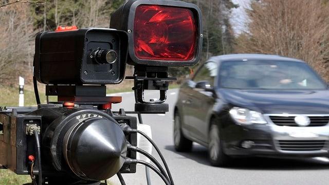 Radar-Gerät der Polizei an einer Strasse und ein Auto, das daran vorbeifährt.