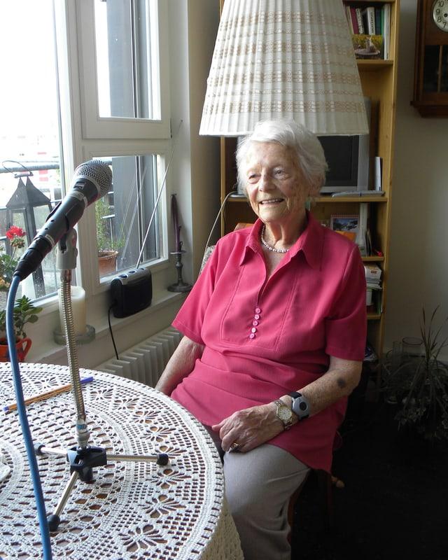 Alice Marti sitzt am Tisch, der mit einer Häkeldecke zugedeckt ist. Ein Mikrofon steht darauf.
