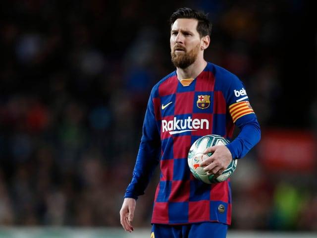 Lionel Messi hält einen Ball in der Hand