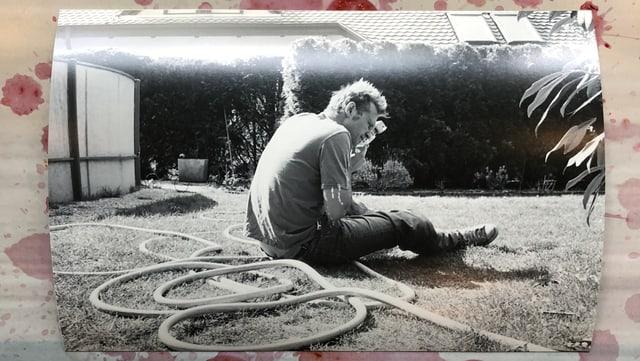 Mann sitzt halb abgewandt auf Rasen, Gartenschlauch neben ihm