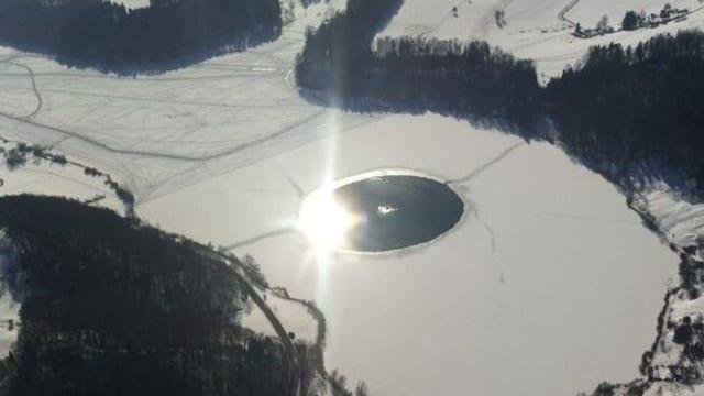 Luftbild vom Türlersee. In der Mitte eine kreisrunde, offene Wasserfläche.