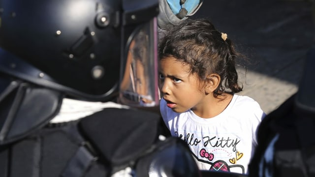 Ein Mädchen beobachtet einen mexikanischen Nationalgardisten