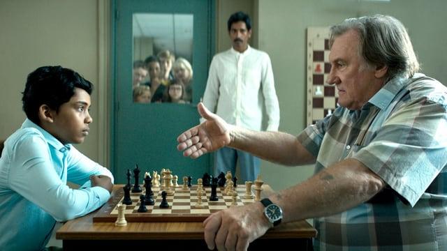 Ein junge aus Bangladesh und ein älterer Mann spielen gegeneinander Schach.