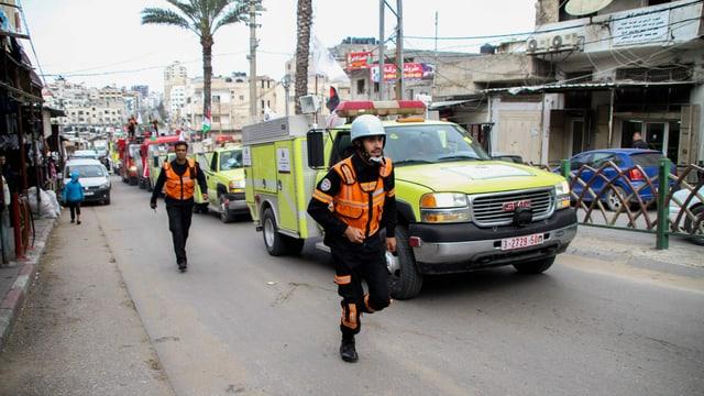 Uniformeirte und Rettungsfahrzeuge in einer Strasse Gazas.