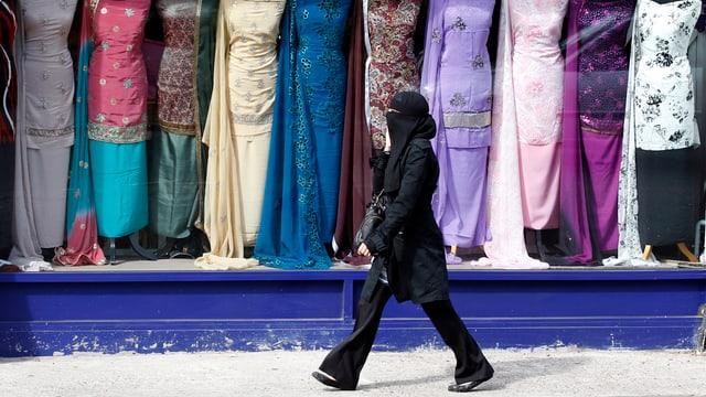 Symbolbild: Eine verschleierte Frau geht vor einem Geschäft mit ausgestellten pakistanischen Frauenkleidern vorbei.