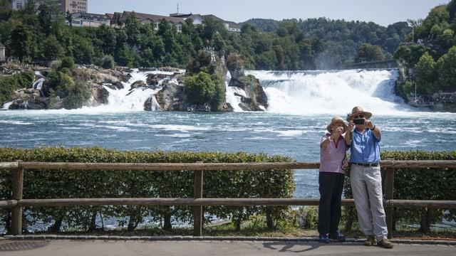 Turists che fan in selfi cun la cascada dal rain davostiers.