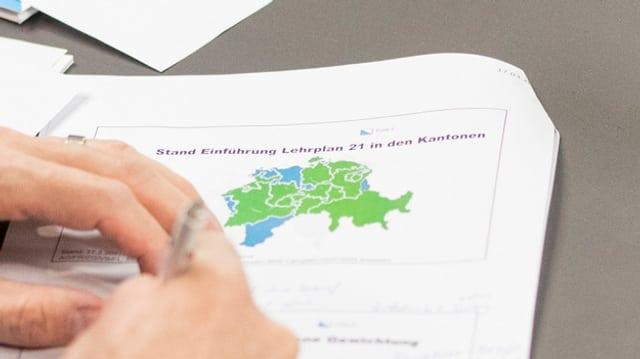 Hände machen Notizen auf einem Blatt mit einer Grafik zum Stand der Einführung des Lehplanes 21