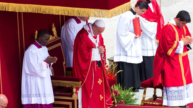 Papst Franziskus in rotem Gewand, mit gefalteten Händen betend