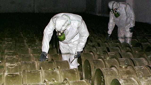 Zwei Männer mit Schutzmasken und Schutzanzügen kontrollieren Fässer, die chemische Kampfstoffe beinhalten.