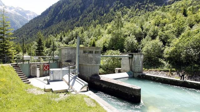 Ein Kraftwerk vor einer gebirgigen Landschaft.