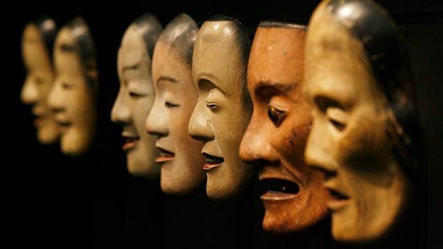 Holzmasken vor schwarzem Hintergrund.