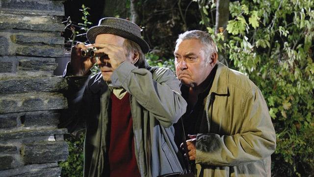 Zwei ältere Männer verstecken sich hinter einer Hauswand. Einer der beiden sieht durch ein Fernrohr.