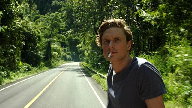 Ein Mann mit Zigarette im Mund steht an einer Strasse im Wald.