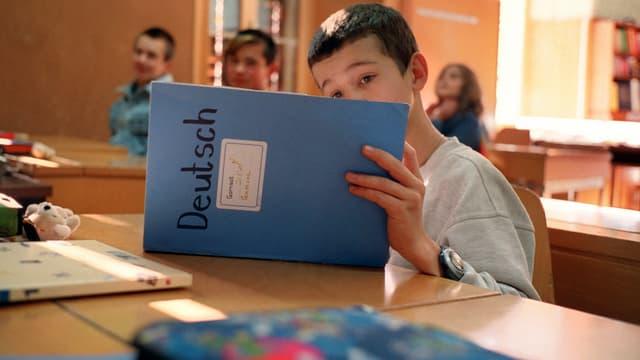 Ein Flüchtlingsjunge sitzt im Schulbank und hat ein Heft mit der Aufschrift Deutsch aufgeschlagen.